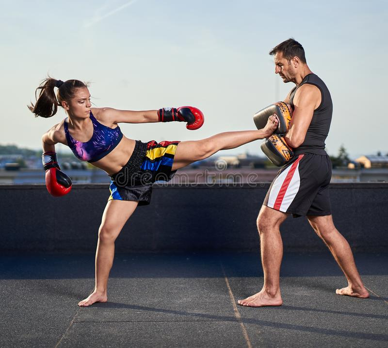 Young woman kickboxer in urban environment, training. Young women kickbox fighter training with her coach on the roof above the city royalty free stock photo