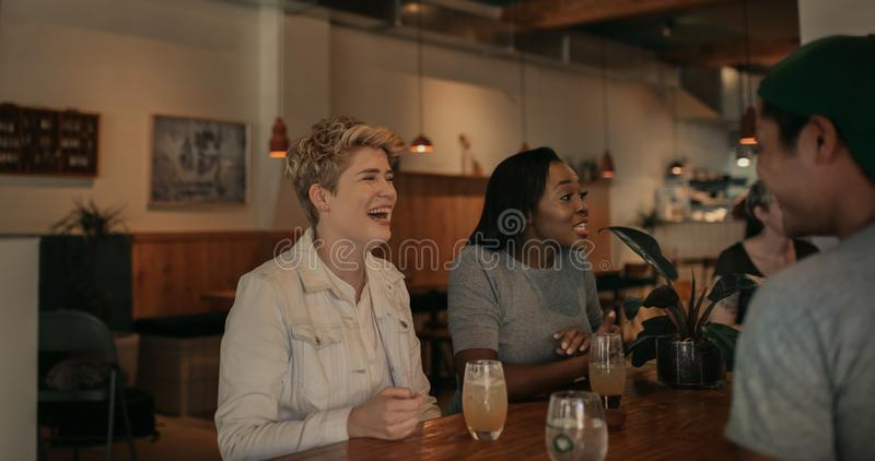 Young woman laughing with her friends in a bar stock photography