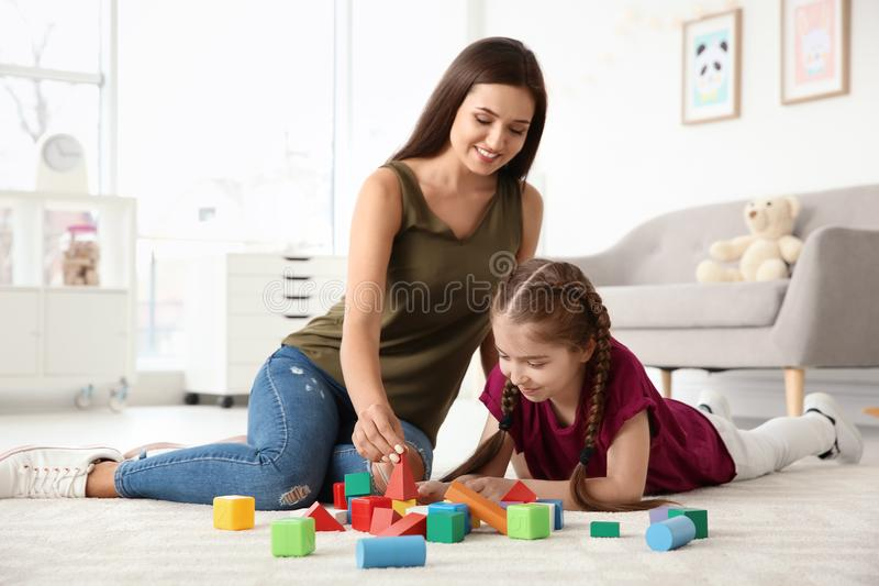 Young woman and little girl with autistic disorder playing stock image