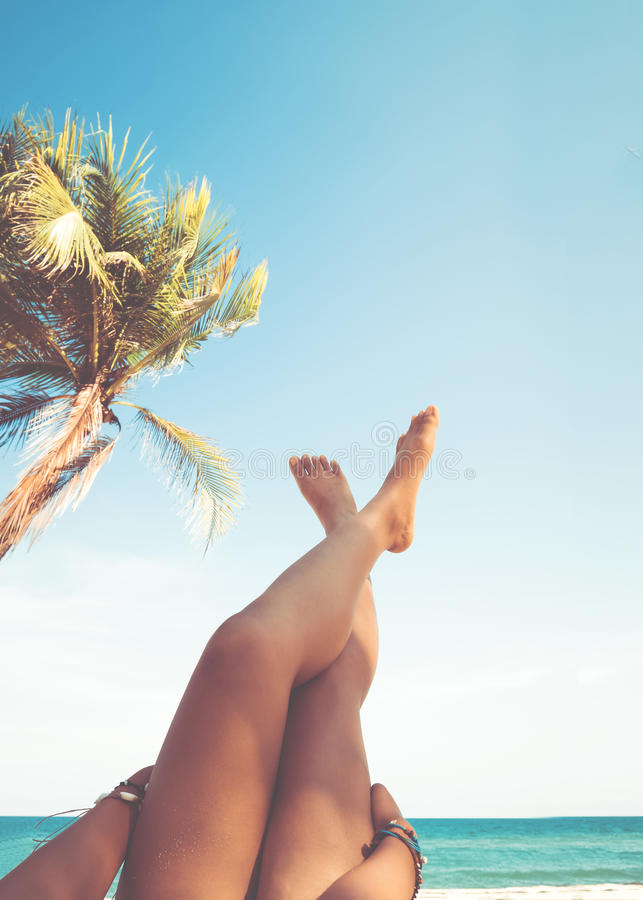 Young women lying on a tropical beach, relax stretching up slender legs tanned. Leisure in summer - Young women lying on a tropical beach, relax stretching up stock images