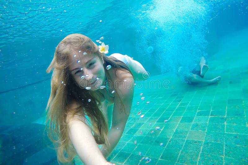 Young woman making selfie under water in the pool. In her hair is a frangipani flower. Against the background a young guy jumped i stock images