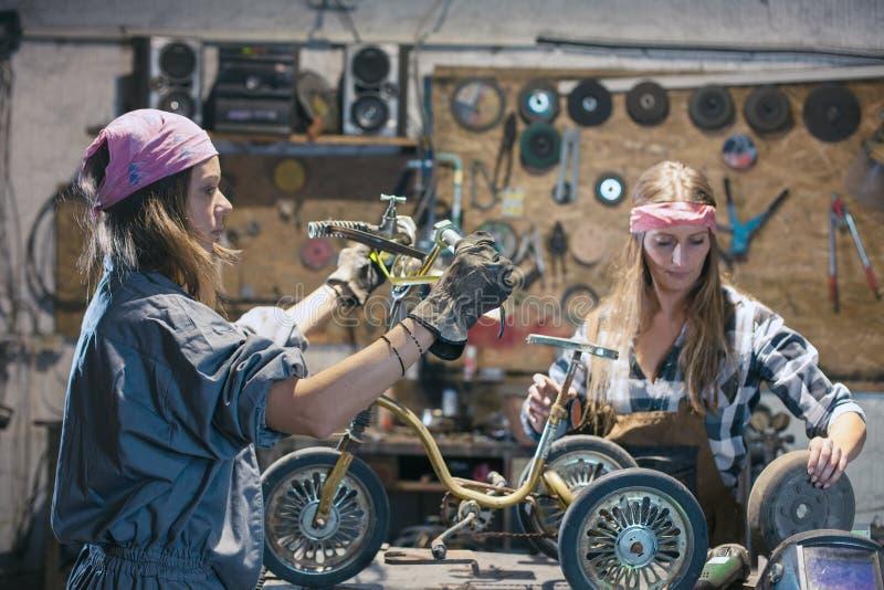 young women mechanics repairing children bicycle in workshop royalty free stock photos