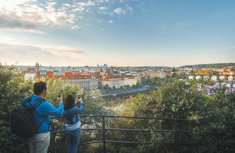 People taking photos with phone with the Prague city stock images