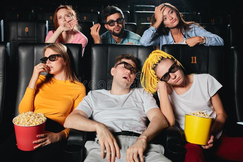 Young women and men expressing negative feeling while watching movie stock image