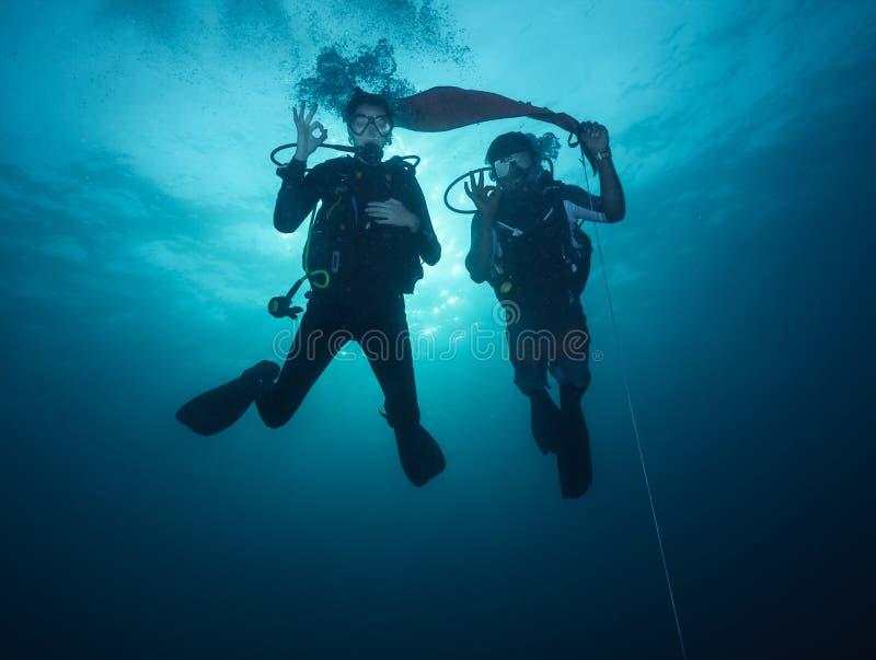 Young woman and man scuba divers exploring stock image