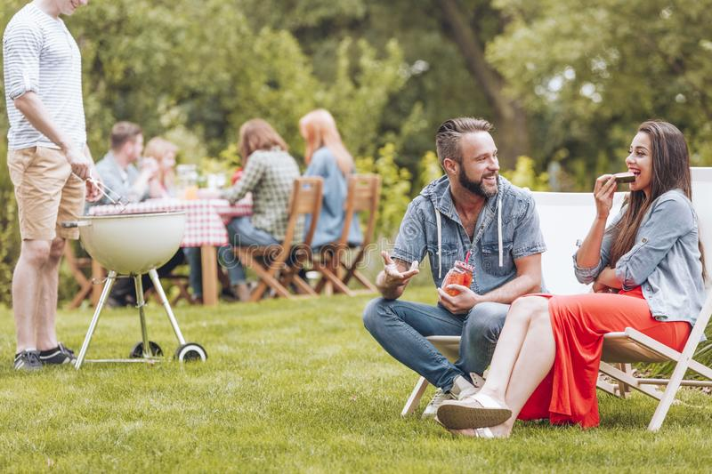 Young woman and man sitting on deck chairs and talking during ga. Young women and men sitting on deck chairs and talking during garden grill party. Other people stock image