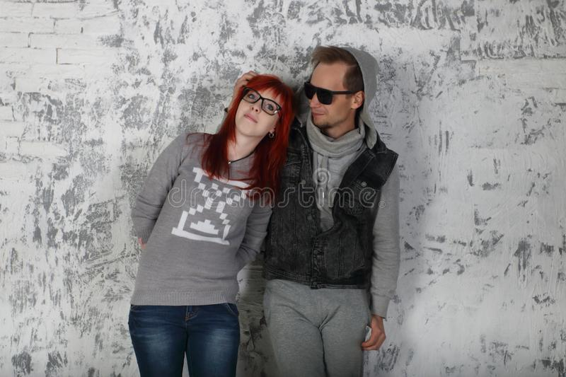 Young woman and man in sunglasses stand near wall stock images
