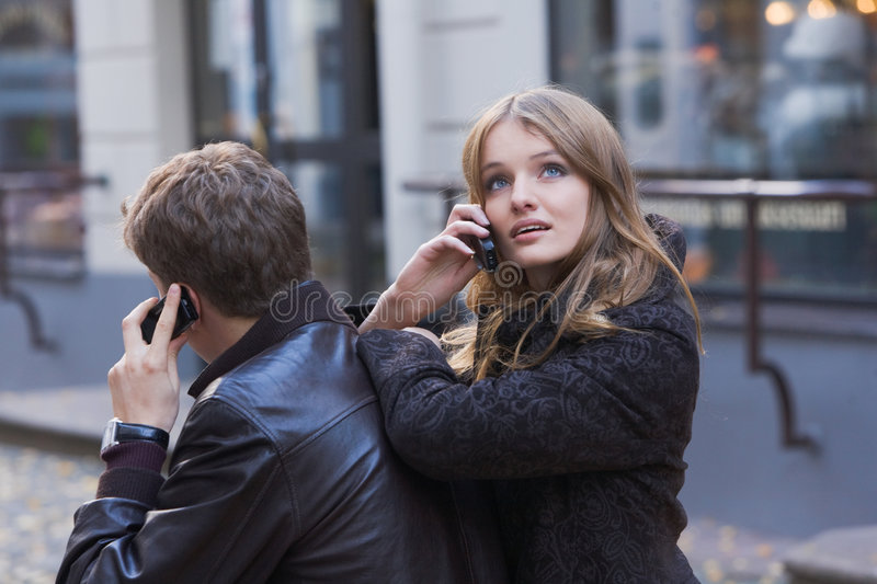 Young women and men talking on mobile phone royalty free stock photo