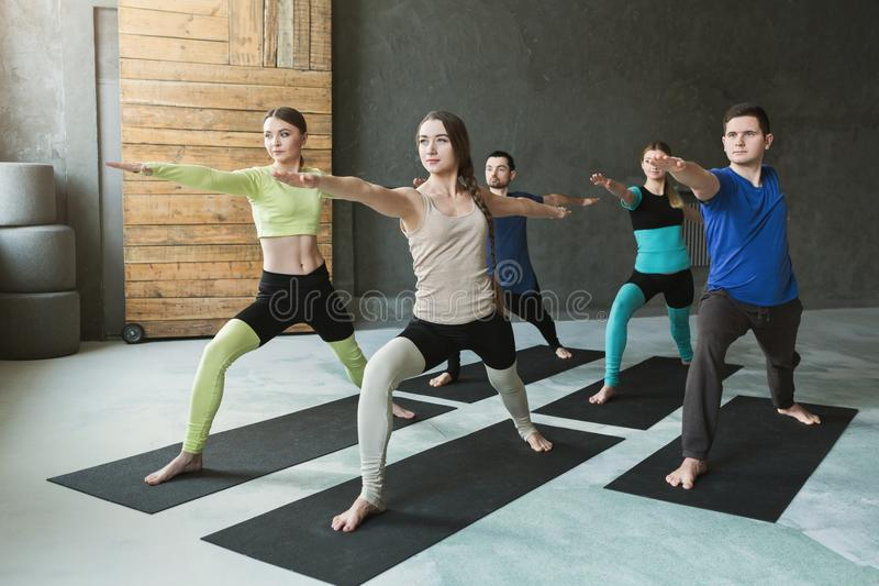 Download Young Women And Men In Yoga Class Doing Stretching Exercises Stock Photo