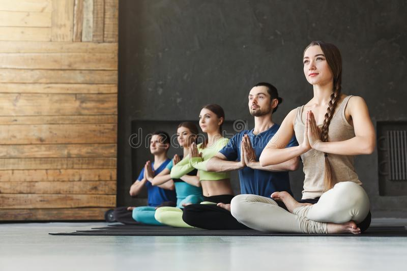 Young women and men in yoga class, relax meditation pose. Young women and men in yoga class, meditation exercises. Lotus pose for relaxation. Healthy lifestyle royalty free stock image
