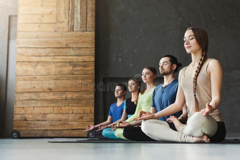 Young women and men in yoga class, relax meditation pose. Young women and men in yoga class, meditation exercises. Lotus pose for relaxation. Healthy lifestyle royalty free stock photos