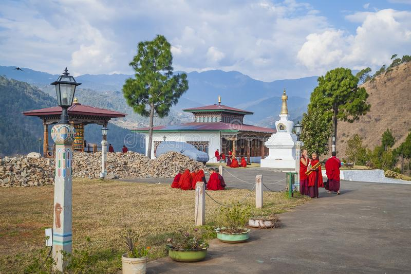 Young women monks of the Buddhist monastery in their traditional red robes before classes next to the prayer wheel. Himalayan moun stock images
