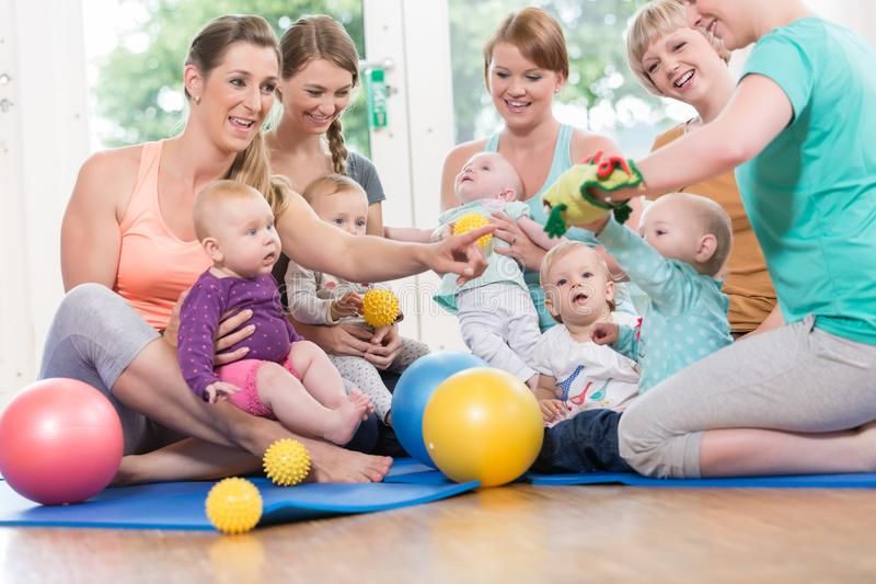 Young women in mother and child group playing with their babies stock photography