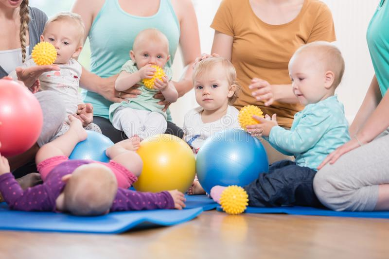 Young women in mother and child group playing with their baby ki stock photography