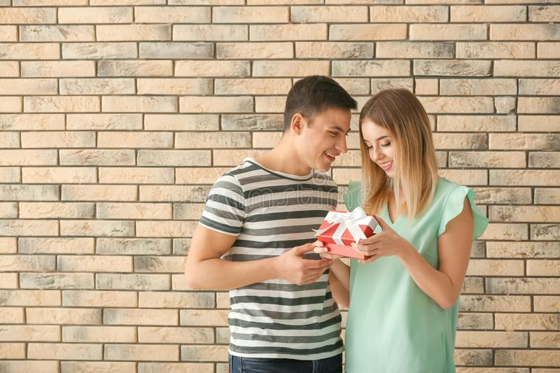 Young woman opening gift box from her boyfriend near brick wall. Young women opening gift box from her boyfriend near brick wall royalty free stock images