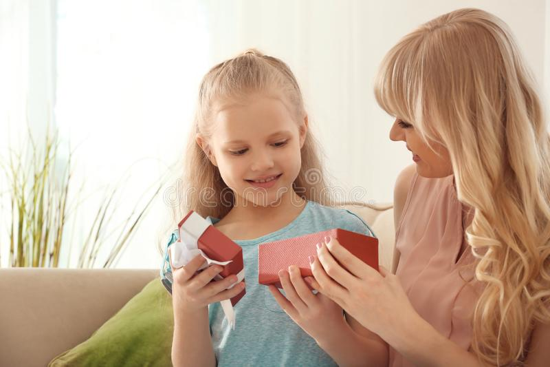 Young woman opening gift from her daughter at home. Mother's day celebration royalty free stock photo