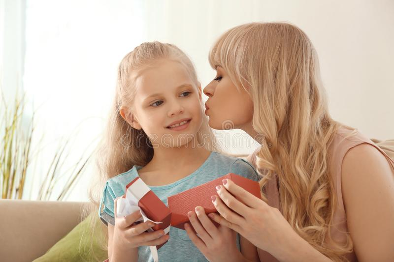 Young woman opening gift from her daughter at home. Mother's day celebration stock photos