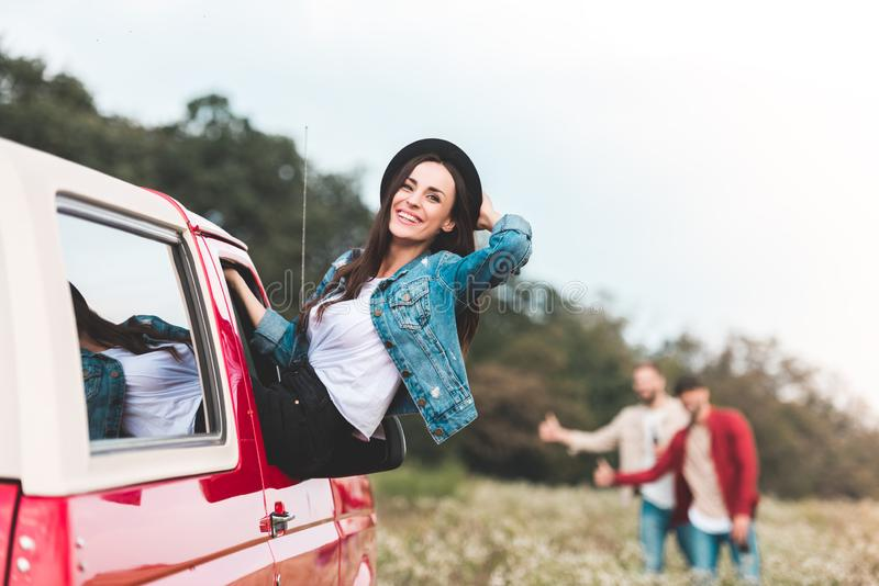 Young woman outstretching from car window while men hitchhiking blurred. Young women outstretching from car window while men hitchhiking blurred on background stock image