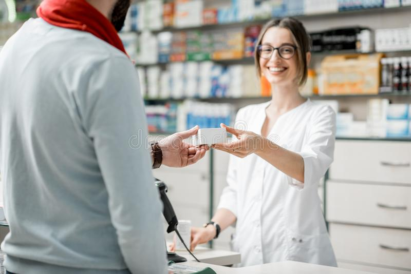 Pharmacist selling medications in the pharmacy store royalty free stock image