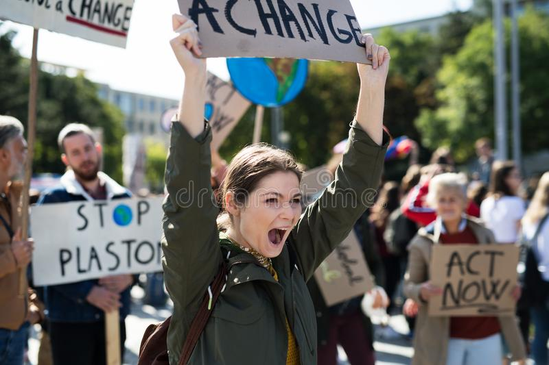 Young woman with placard and poster on global strike for climate change. Young women with placard and poster on global strike for climate change, shouting royalty free stock photography