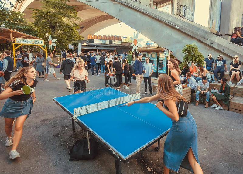 Young women playing ping-pong outside of huge club in urban area stock photography