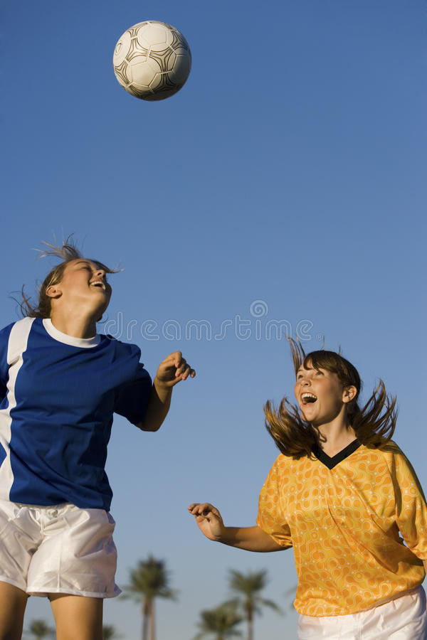 Young Women Playing Soccer. Rival female soccer players heading football against sky royalty free stock photography