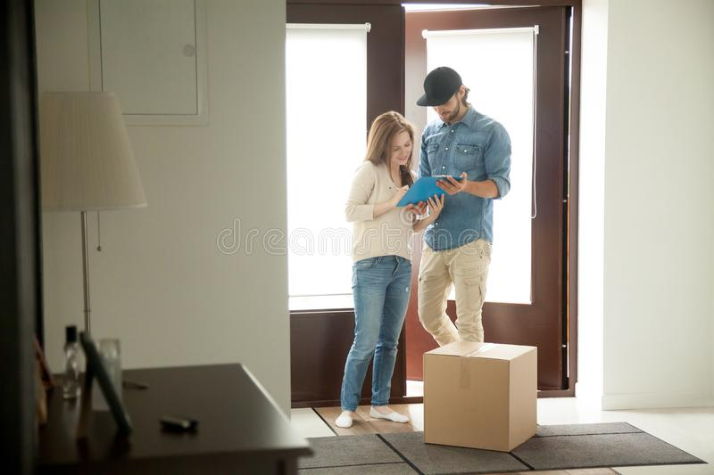 Young woman putting signature receiving parcel from courier at h. Young women putting signature receiving cardboard box from courier at home, receiver singing stock photography