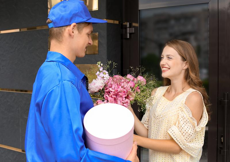 Young woman receiving beautiful flowers and gift from delivery man outdoors royalty free stock photo