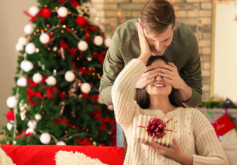 Young woman receiving Christmas gift from her husband at home royalty free stock photography