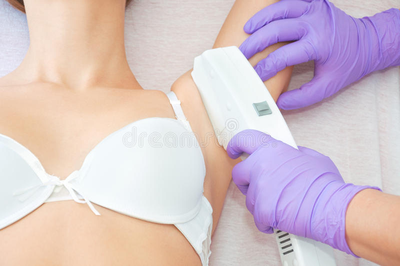 Young woman receiving epilation laser treatment royalty free stock photo