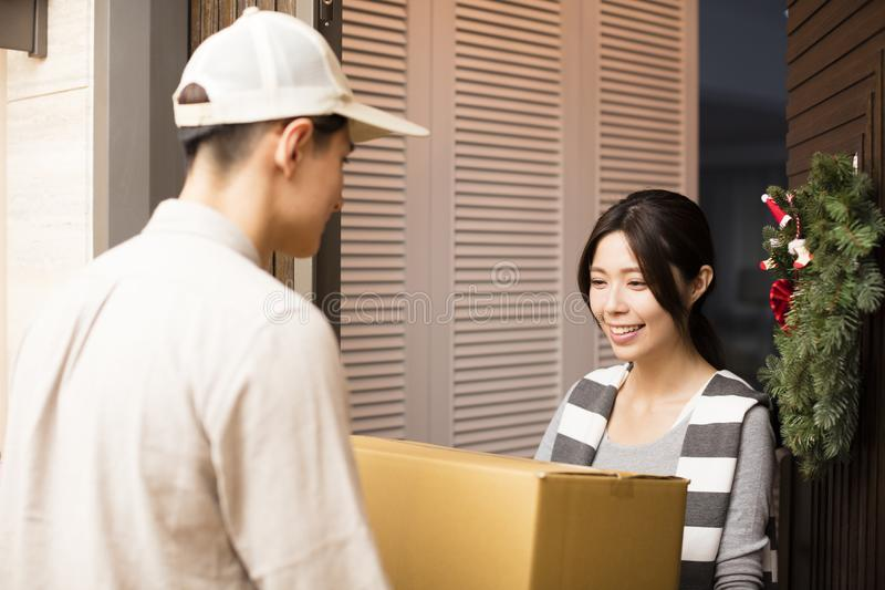 Woman receiving package from delivery man. Young women receiving package from delivery man stock photos