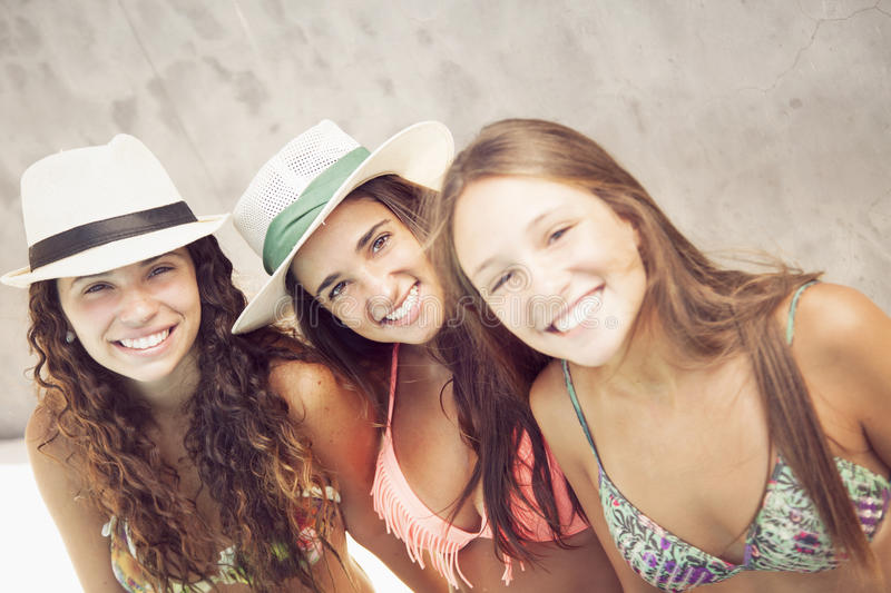 Young women relaxing by poolside stock photos