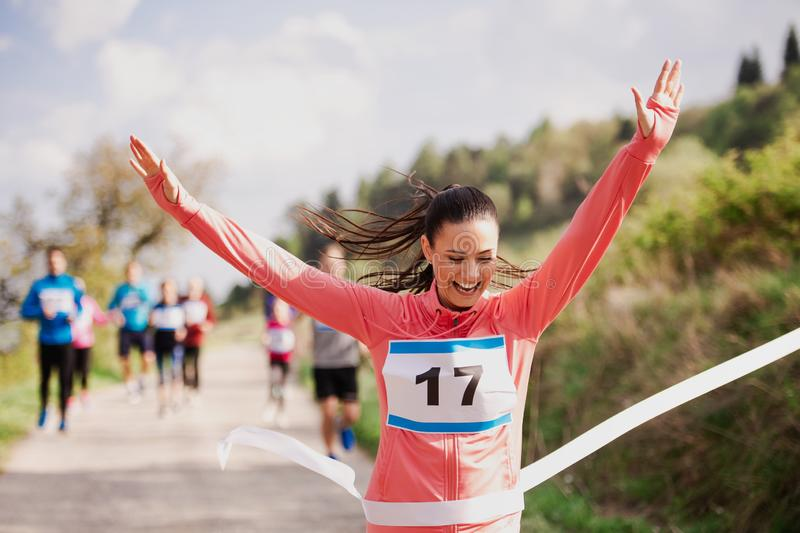 Young woman runner crossing finish line in a race competition in nature. A young women runner crossing finish line in a race competition in nature, arms raised royalty free stock images