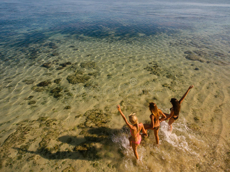 Young women running into the sea stock photos