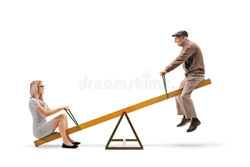 Young woman and a senior man playing on a seesaw stock photography