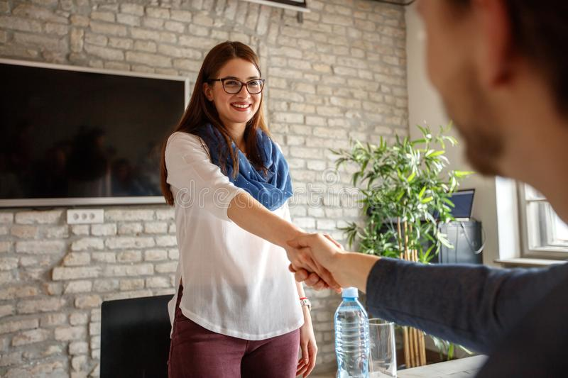 Woman shaking hands with male. Young women shaking hands with male on job stock photos