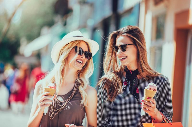 Young women with shopping bags and ice cream having fun stock image