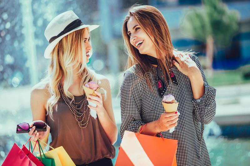 Young women with shopping bags and ice cream having fun stock images