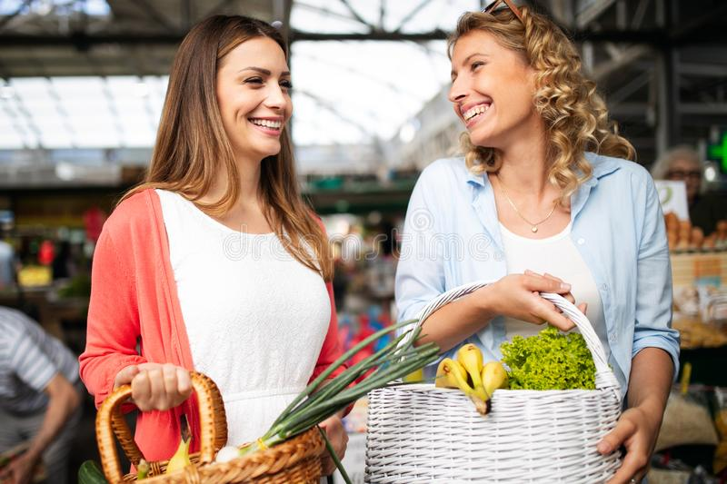 Young women shopping on the market healthy vegetables and fruits stock images