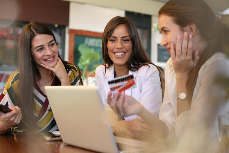 Young women shopping online with credit card. Friends in cafe using credit card for online shopping stock photography