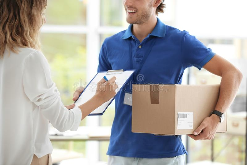 Young woman signing for delivered parcel indoors. Young women signing for delivered parcel indoors. Courier service royalty free stock images