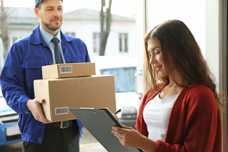 Young woman signing documents after receiving parcel. Young women signing documents after receiving parcels from courier stock photography