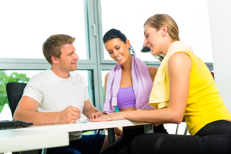 Young women signing up for gym. Membership royalty free stock image