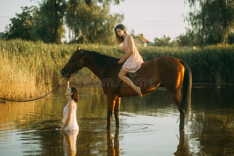 Woman sits astride a horse and other woman bathes in river. A young women sits astride a horse and other women bathes in the river stock images