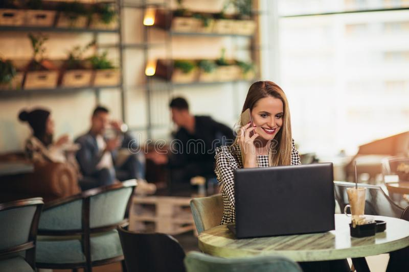 Young woman sitting in front of open laptop computer in cafe bar. Young women sitting in front of open laptop computer in cafe bar using phone royalty free stock images