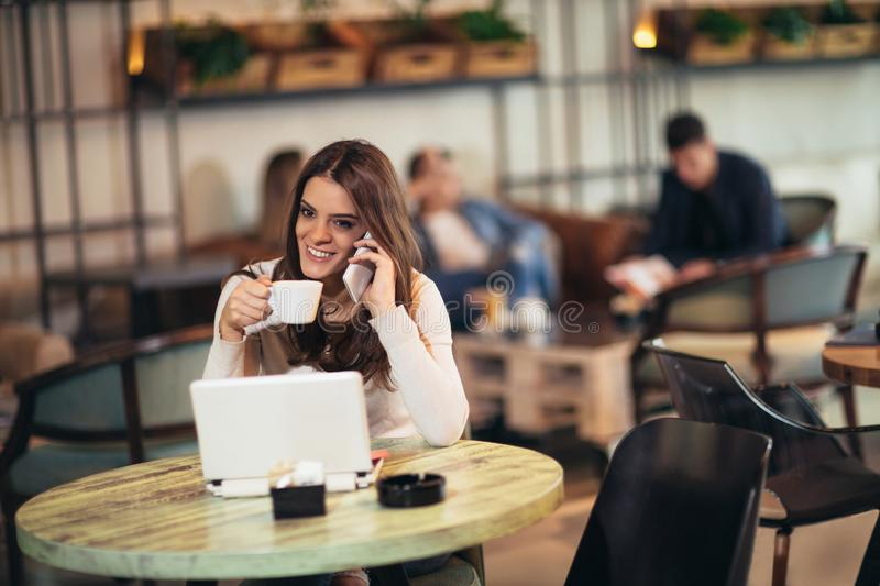 Young woman sitting in front of open laptop computer in cafe bar stock photos
