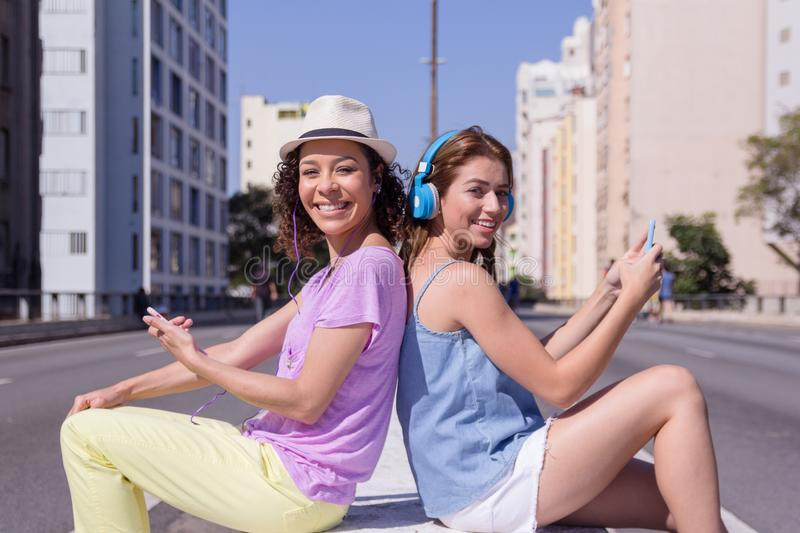 Young women smiling with colorful clothingusing technology outdo royalty free stock photos