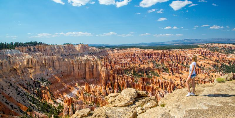 Young women standing by the scenic view of stunning red sandstone hoodoos stock photo