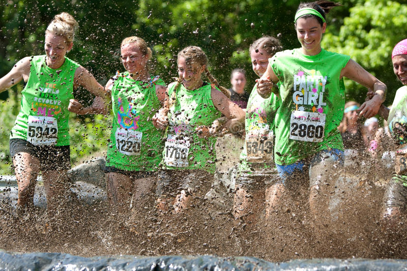 Young Women Stomp Through Mud Pit In Obstacle Course Run. Atlanta, GA, USA - April 28, 2012: A group of young women join arms and stomp through a mud pit royalty free stock photos