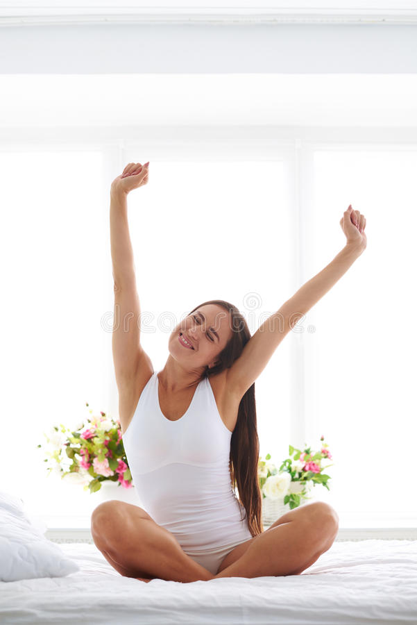 A young women stretching after waking up royalty free stock photos